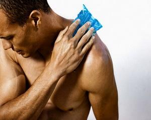 Man applying cold pack to sore shoulder
